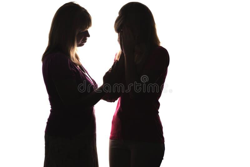 La silhouette de pleurer d'adolescent, et de mère soulage le daugter photos libres de droits