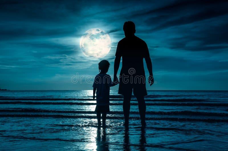 La silhouette de se tenir d'enfant remet son père, se tenant dans le Se image stock