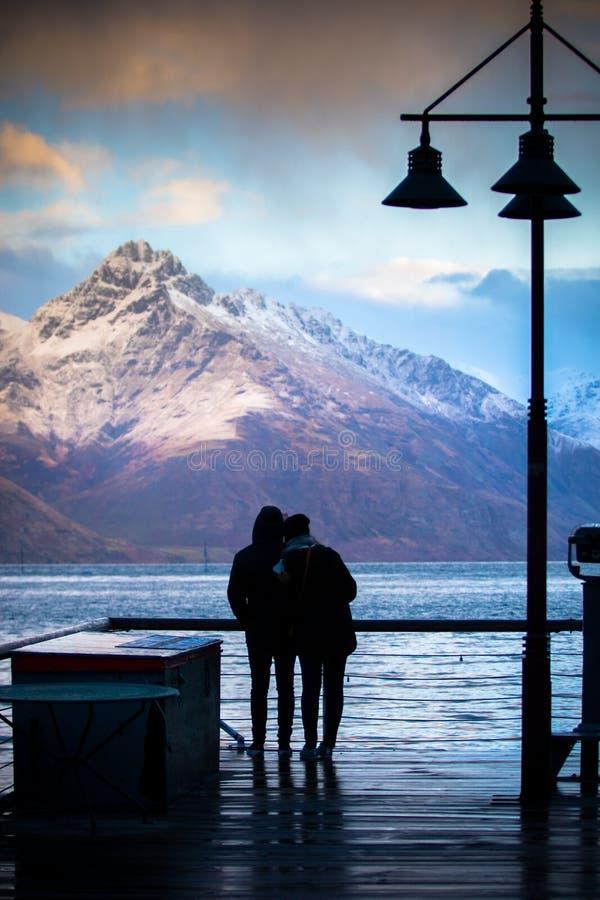 La silhouette des couples aiment se tenir au point de vue de lac de wakatipu photos libres de droits