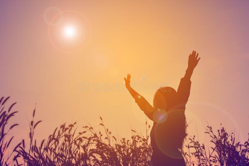 La silhouette des femmes heureuses ouvrent la main dans le domaine d'herbe au ciel su photo stock
