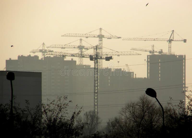 La silhouette des maisons et beaucoup de grues les construisent image libre de droits