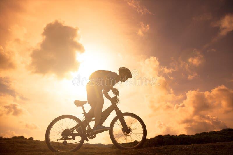La silhouette du cavalier de bicyclette de montagne sur la colline images stock