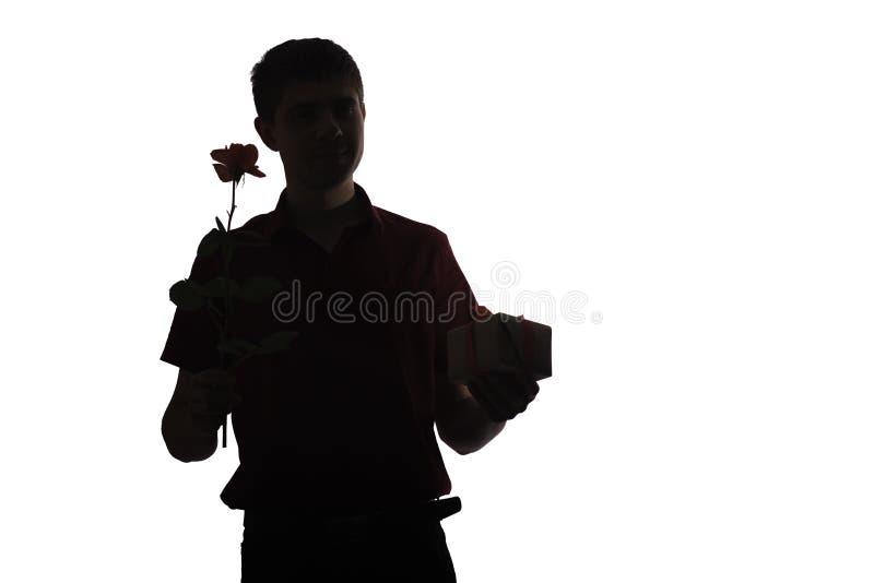La silhouette du jeune homme avec un boîte-cadeau et une fleur rose pour son aimé, garçon félicite sur le fond d'isolement blanc, images libres de droits