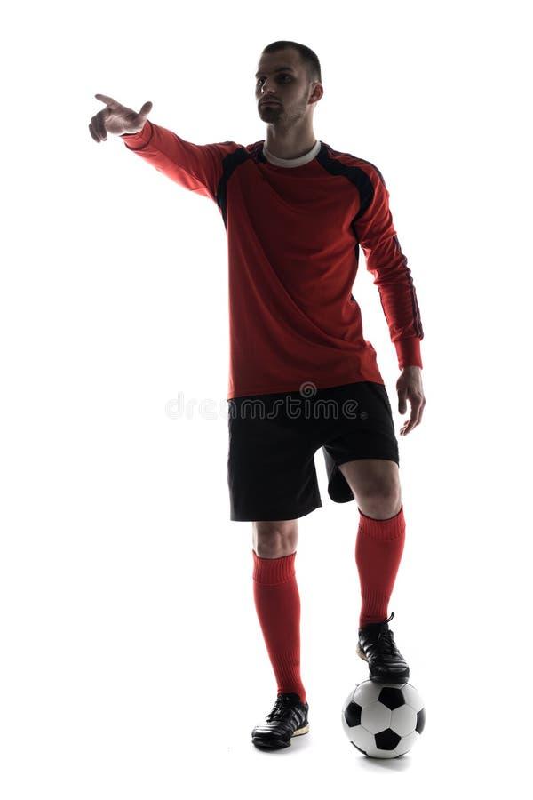 La silhouette du jeune joueur de football s'est dirigée avec le doigt avec du ballon de football d'isolement sur le fond blanc photos libres de droits