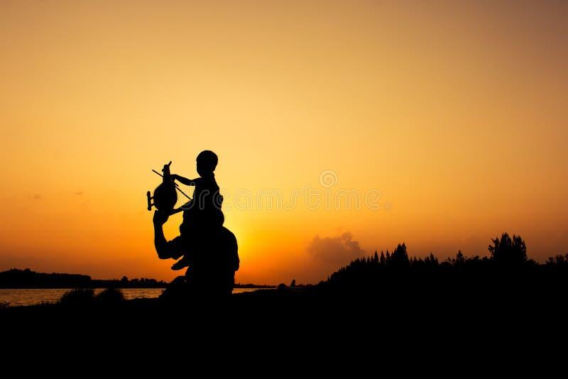 La silhouette du papa et le fils prévoient le coucher du soleil plat photos stock