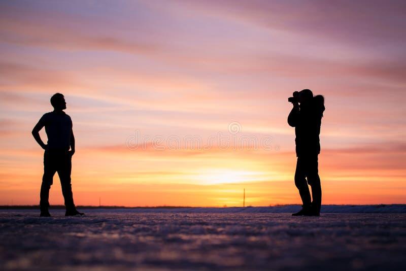 La silhouette du photographe et de l'homme à photos stock
