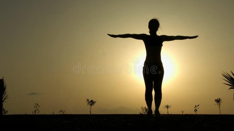 La silhouette femelle faisant le yoga s'exerce pour l'harmonie du corps et de l'esprit sains image libre de droits