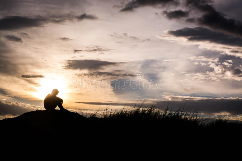 La silhouette triste de garçon s'est inquiétée sur le pré au coucher du soleil, la silhouette c photographie stock