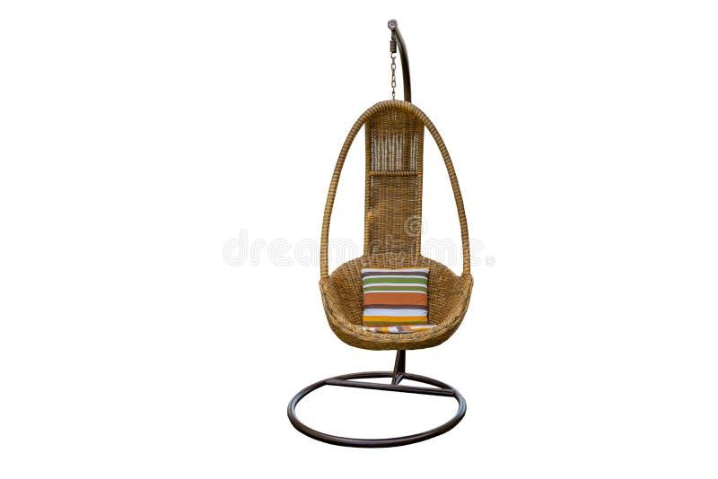 La silla colgante de mimbre, oscilación que cuelga en una cadena con el orang amortigua la almohada anaranjada aislada en el fon fotografía de archivo