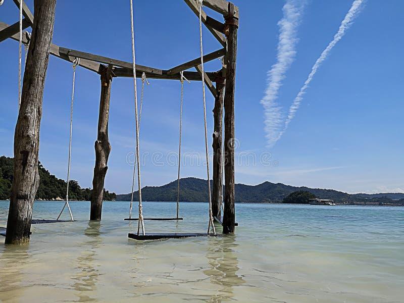 La silla del oscilación en la playa foto de archivo