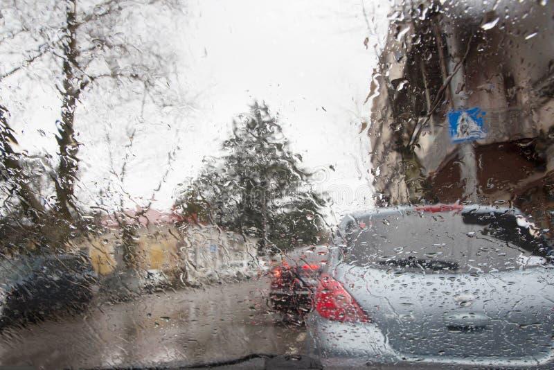 La silueta borrosa del coche vista a través del agua cae en el parabrisas del coche Días lluviosos imagen de archivo