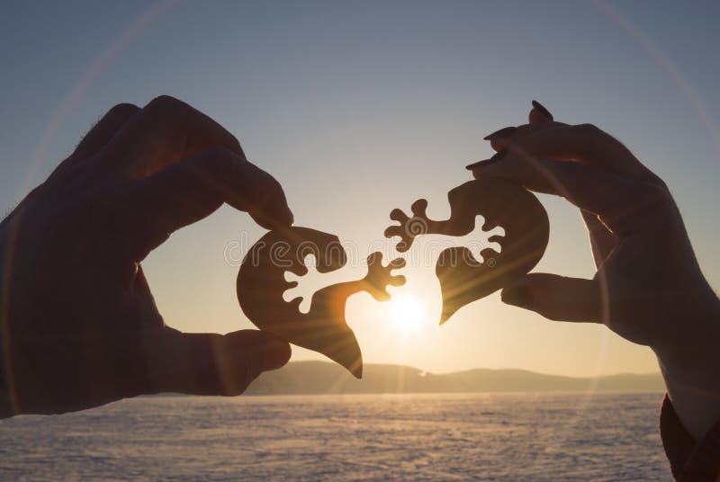 La silueta conecta el corazón dos pedazos de rompecabezas en manos de amantes contra la perspectiva de salida del sol foto de archivo