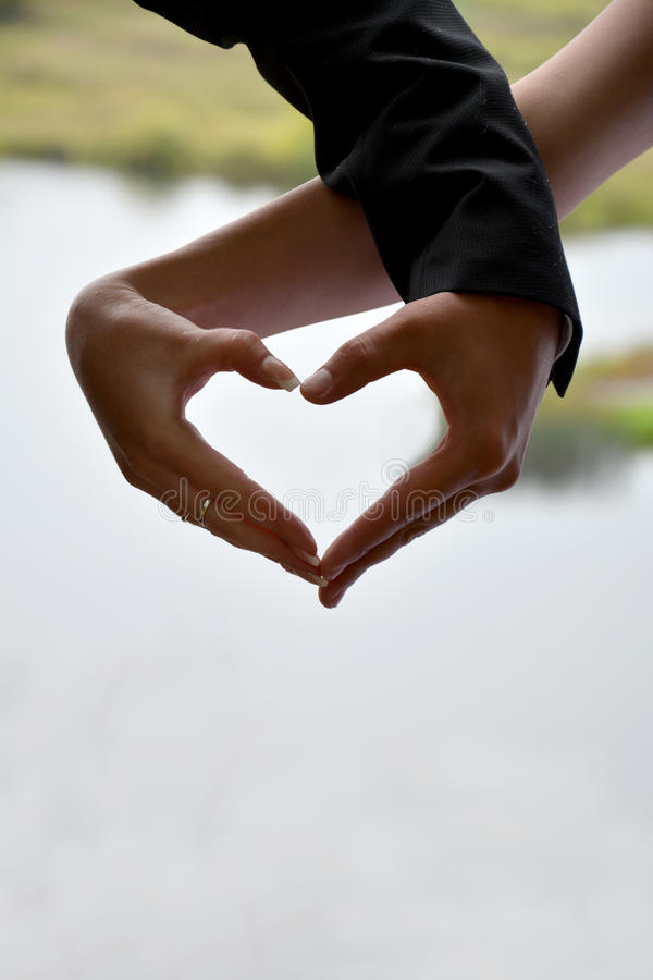 La silueta de dos manos de la novia y del novio en corazón forma imagenes de archivo