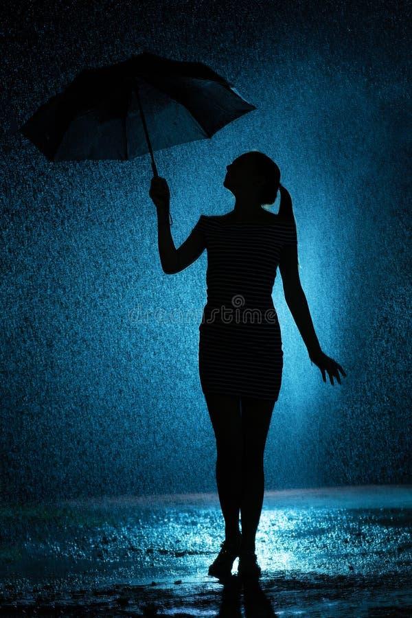 La silueta de la figura de una chica joven con un paraguas bajo la lluvia, una mujer joven es feliz a los descensos del agua, tie fotos de archivo libres de regalías