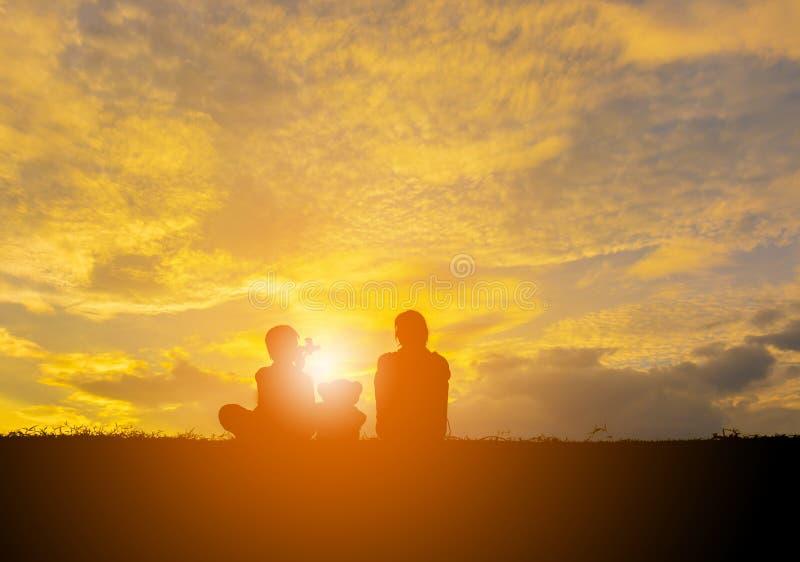 La silueta de goza de los niños que juegan y de los osos de peluche con puesta del sol imagen de archivo libre de regalías