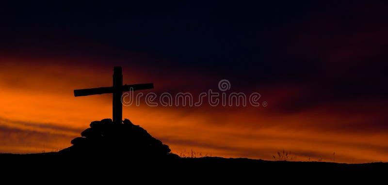 La silueta de la cruz de madera en fondo ardiente del cielo imagenes de archivo