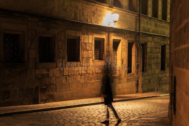 La silueta de la muchacha en el movimiento el noche iluminó la calle imagenes de archivo