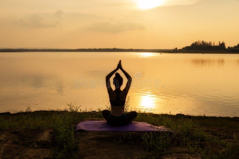 La silueta de la mujer joven medita mientras que practica yoga y se relaja fotos de archivo libres de regalías