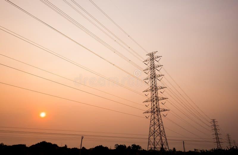 Torres de la transmisión de poder con puesta del sol foto de archivo