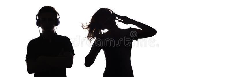 La silueta de las figuras adolescentes en auriculares que escuchan la música, el individuo y la muchacha están bailando con las m fotos de archivo