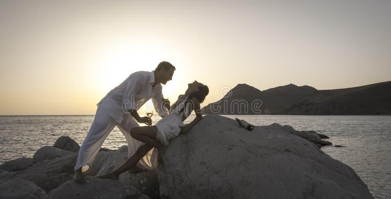 La silueta de los pares felices jovenes que se divierten en la playa oscila en la salida del sol foto de archivo libre de regalías