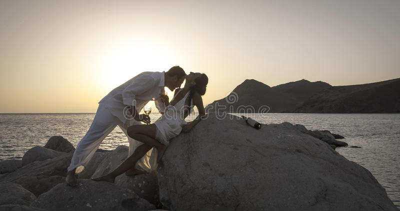 La silueta de los pares felices jovenes que se divierten en la playa oscila en la salida del sol imagen de archivo