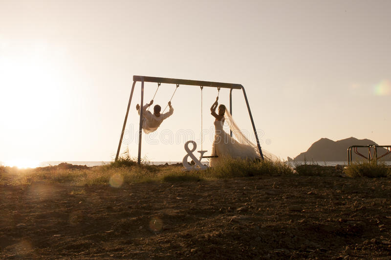 La silueta de los pares jovenes que jugaban en el oscilación fijó en la puesta del sol imagenes de archivo