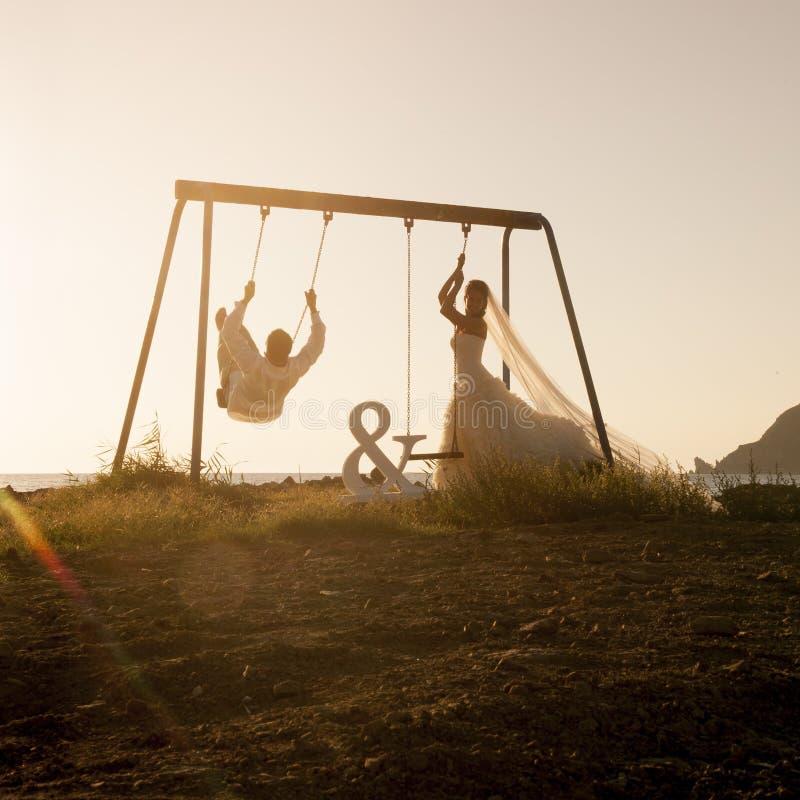La silueta de los pares jovenes que jugaban en el oscilación fijó en la puesta del sol foto de archivo libre de regalías