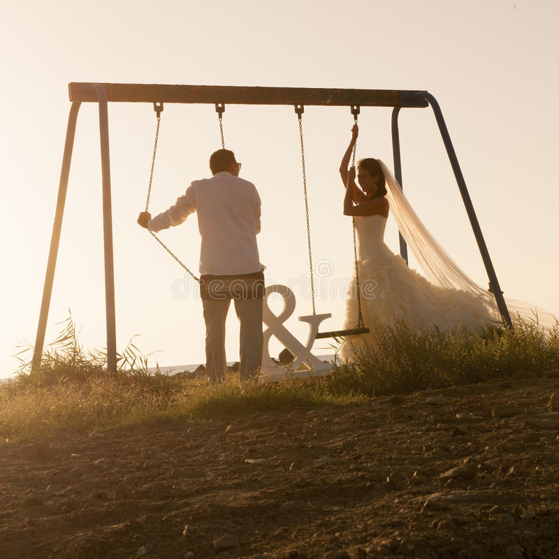 La silueta de los pares jovenes que jugaban en el oscilación fijó en la puesta del sol imágenes de archivo libres de regalías