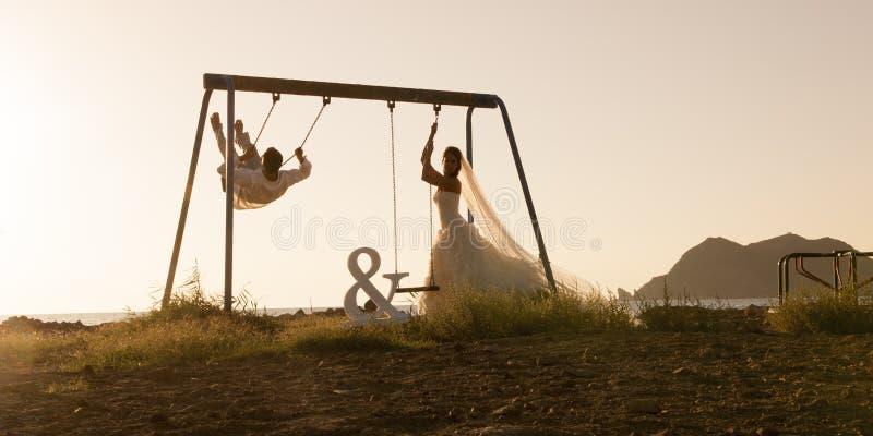 La silueta de los pares jovenes que jugaban en el oscilación fijó en la puesta del sol fotografía de archivo