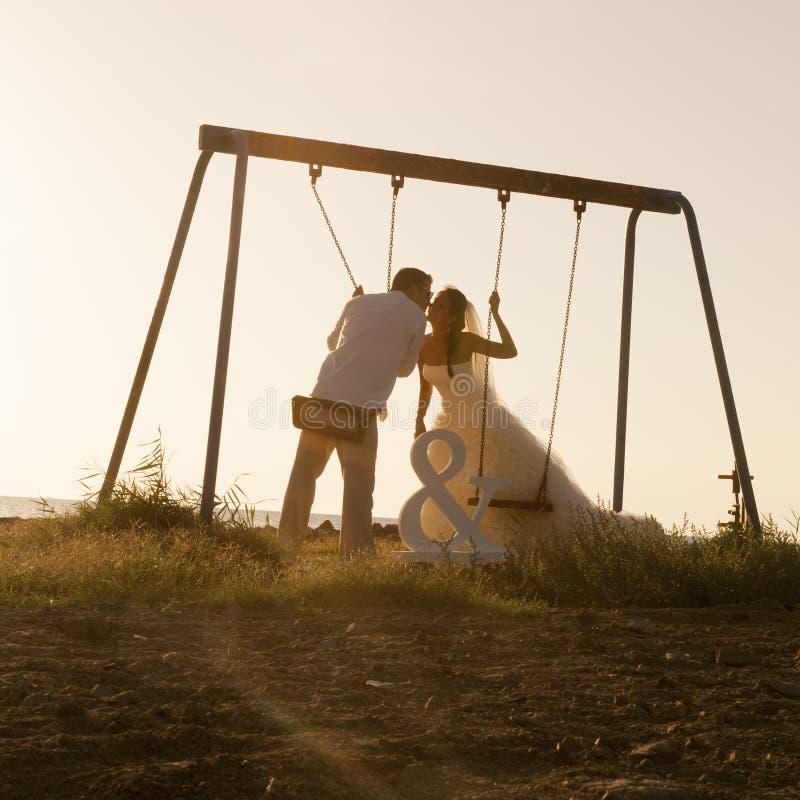 La silueta de los pares jovenes que jugaban en el oscilación fijó en la puesta del sol imagen de archivo libre de regalías