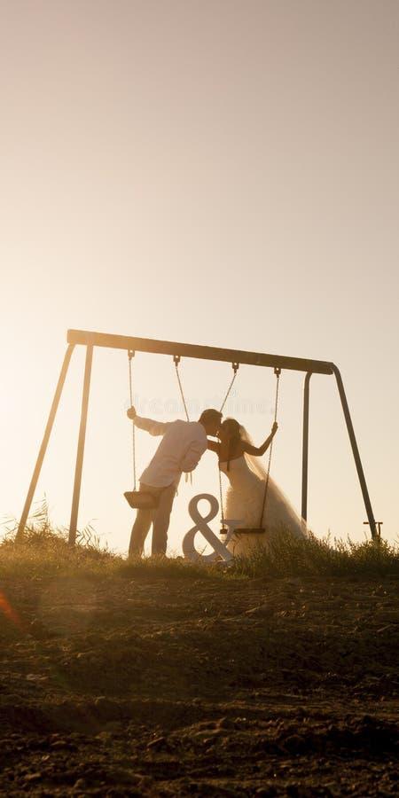 La silueta de los pares jovenes que jugaban en el oscilación fijó en la puesta del sol fotografía de archivo libre de regalías