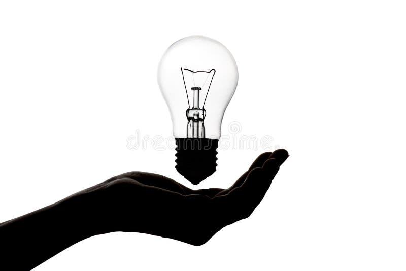 la silueta de la mano con una lámpara incandescente, bulbo del pensamiento, concepto de idea en blanco aisló el fondo foto de archivo libre de regalías