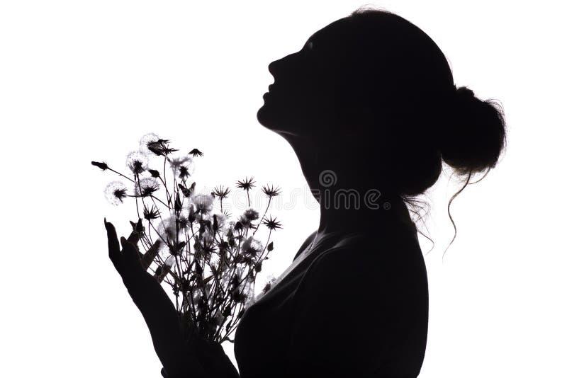 La silueta de la muchacha con un ramo de flores, perfil de la cara de la mujer que miraba hacia arriba en un blanco aisló el fond imágenes de archivo libres de regalías