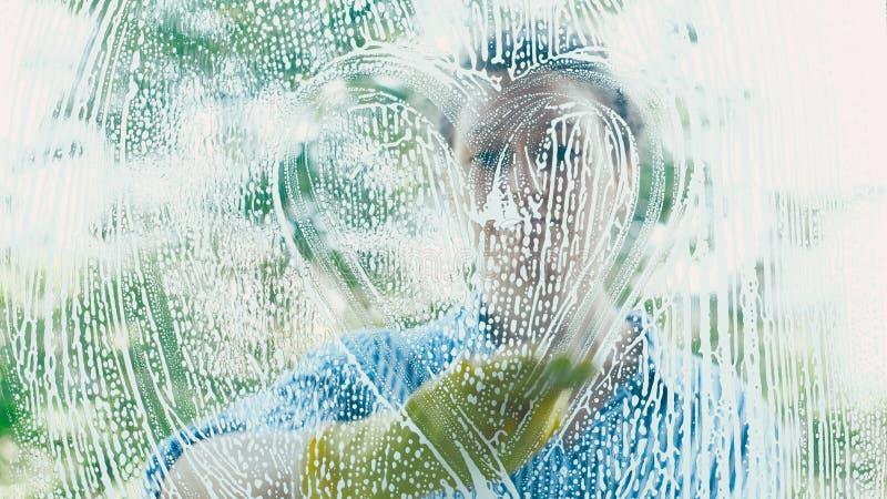 La silueta de la mujer joven pinta el corazón blanco de la espuma en ventana foto de archivo libre de regalías