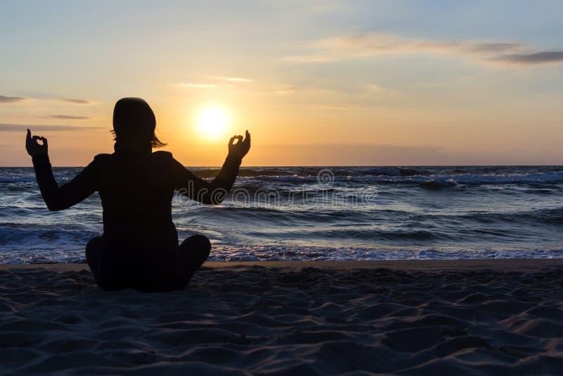 La silueta de la mujer joven que se sienta cómodamente, medita en la actitud de la yoga del loto al aire libre, en la playa imágenes de archivo libres de regalías