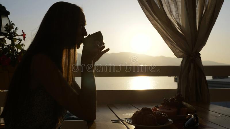 La silueta de la mujer joven se sienta en un café con vistas panorámicas de la bahía del mar fotos de archivo libres de regalías