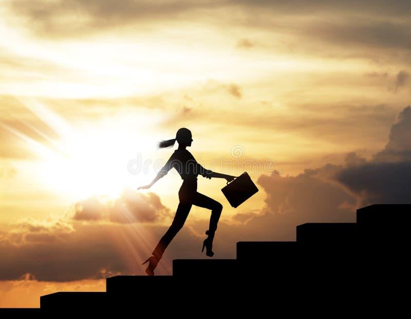 La silueta de la mujer se alza en las escaleras de la palabra del negocio imágenes de archivo libres de regalías