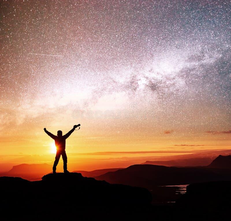 La silueta de la mujer se está colocando encima de la montaña y está señalando a la vía láctea antes de salida del sol y está goz imagenes de archivo