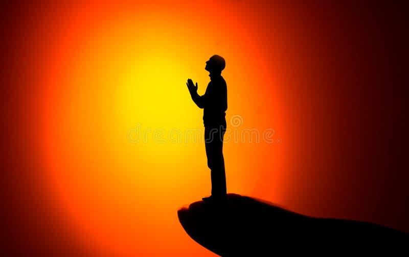 La silueta de un hombre con las manos aumentó en la puesta del sol Rezo imagen de archivo libre de regalías