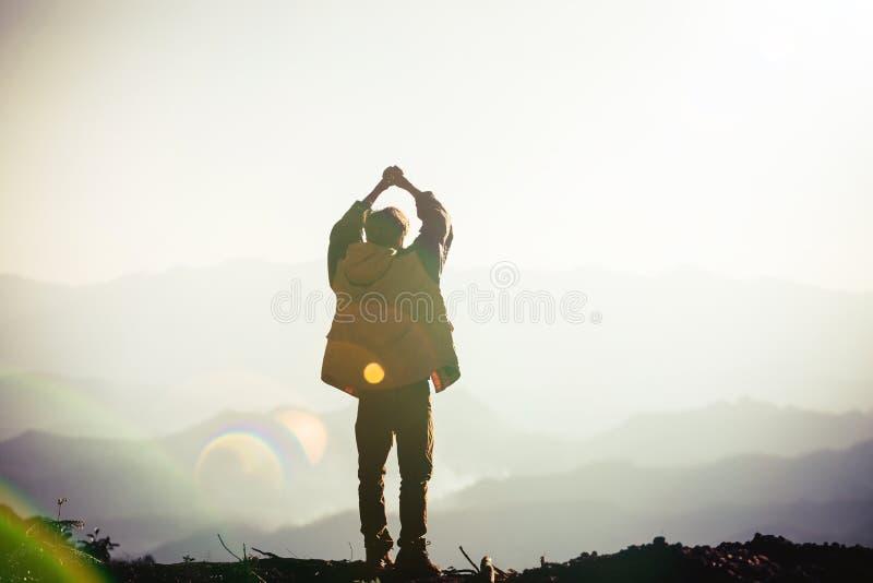 La silueta de un hombre con las manos aument? en la puesta del sol fotografía de archivo libre de regalías