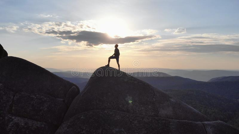 La silueta de un hombre que se coloca triunfante en un top de la montaña en la puesta del sol fotografía de archivo
