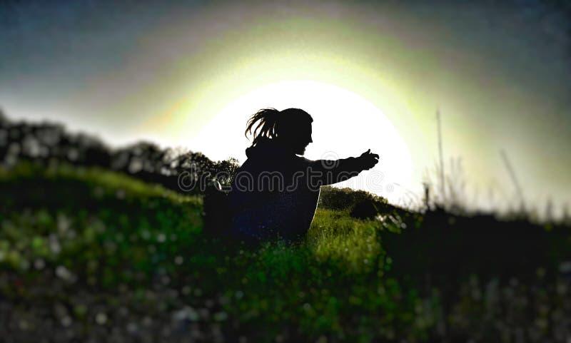 la silueta de un Rastafarian que se sienta en la hierba en la puesta del sol imagen de archivo libre de regalías