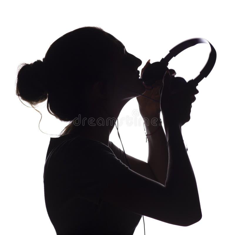 La silueta de una muchacha pone los auriculares y escuchar la música, perfil principal del amante de la música joven en un fondo  foto de archivo libre de regalías