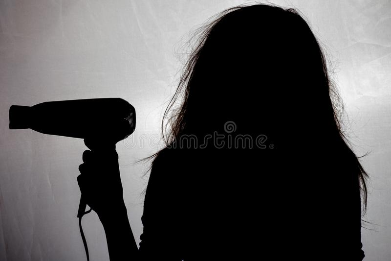 La silueta de una mujer con el pelo enredado y dañado, un concepto de belleza y atención sanitaria foto de archivo