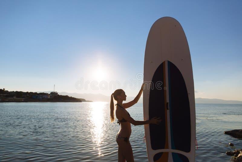 La silueta de una mujer hermosa encendido se levanta el tablero de paleta SORBO, forma de vida del concepto, deporte fotos de archivo