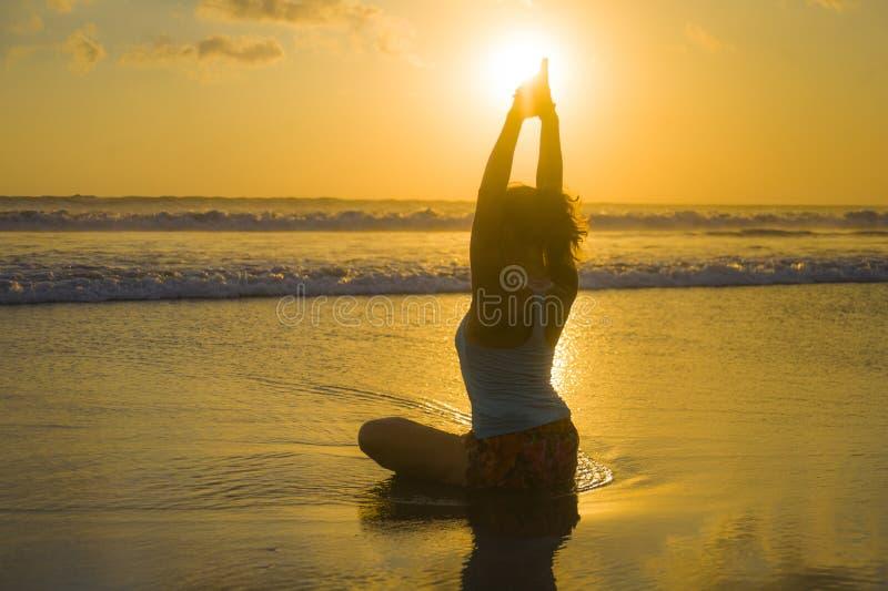 La silueta del ajuste de los jóvenes y la mujer atractiva del deporte en yoga de la puesta del sol de la playa practican el entre imagen de archivo