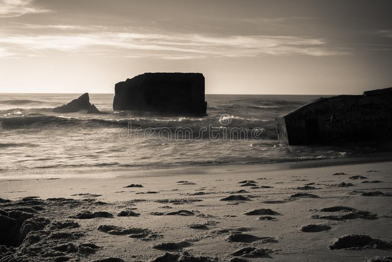 La silueta del blocao de la guerra en paisaje de oro caliente hermoso de la puesta del sol con salpicar agita en fondo atlántico  fotografía de archivo