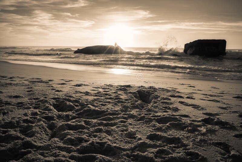 La silueta del blocao de la guerra en paisaje de oro caliente hermoso de la puesta del sol con salpicar agita en fondo atlántico  fotografía de archivo libre de regalías