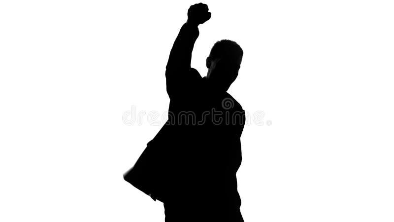 La silueta del hombre de negocios aumenta el puño para arriba, celebra el éxito, orgulloso del logro imágenes de archivo libres de regalías